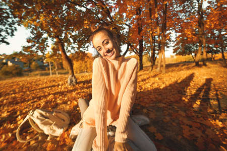 POV, first person view joyful woman in cozy sweater at sunlight autumn park witn colorful foliage, bright fallen leaves on backgroung. Autumn outdoors portrait.