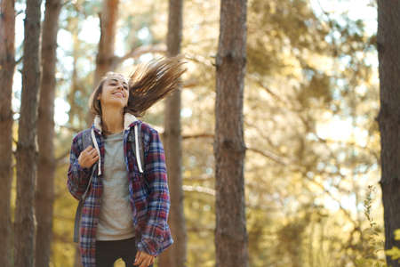motion portrait casual hipster woman in woods with flying long hair. Concept people and nature, adventure