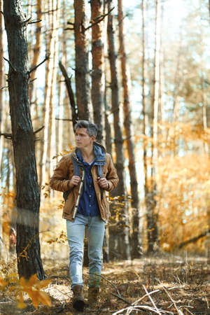 full leght portrait tourist hiker man in forest with backpack, walking in woods at autumn. Concept hiking, people in nature