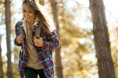 motion portrait smiling traveler woman in woods with backpack, hiking in forest at autumn. Concept people and nature, adventure Imagens