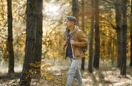 traveler casual style man walking in woods with backpack, single hiking in autumn forest. Concept hiking people in nature Imagens
