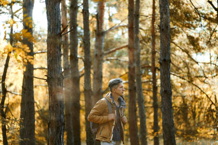casual style man in autumn woods with backpack, single hiking in depths of a forest