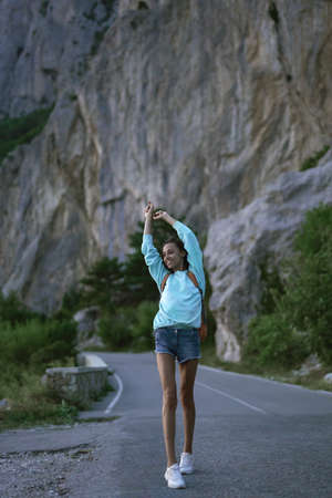 Full length portrait happy traveler woman walks alone on mountain road at evening ,raised hands. Concept freedom and wanderlust