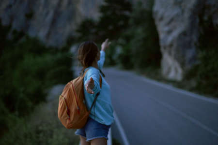 back view girl with backpack stands on road with mountains on background at evening, Follow me, first person view, focus on hand Imagens