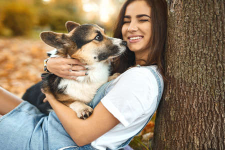 Joyful brunette woman together with cute Welsh Corgi Pembroke dog laughing and having fun in a autumn park outdoors, colorful foliage on background. Concept friendship with dog and human Imagens