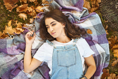 Beautiful stylish woman lying on cozy blanket in a park, colorful fallen leaves around. Autumn bright outdoors portrait. Imagens