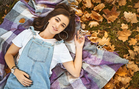 top view lying woman on cozy coverlet in a park, colorful fallen leaves around. woman smiling to camera. autumn outdoors portrait