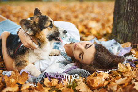 Young female owner huging pet and lying on foliage at autumn park. young woman together with Welsh Corgi dog outdoors at weekend