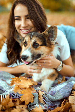 portrait happy woman with her pet Welsh Corgi dog at autumn park outdoors. fallen orange foliage on background. Cute moments pets and human.
