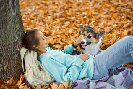girl with her pet Welsh Corgi dog lying on foliage at autumn park, spending time together outdoors. Imagens