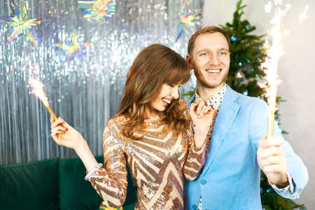 Happy beautiful couple celebrating Christmas or New Year, having fun with sparklers over silver shiny background