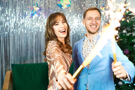 Brightfull expressions of happy emotions, laughing and celebrating together, couple having fun with sparklers over silver shiny background. Imagens
