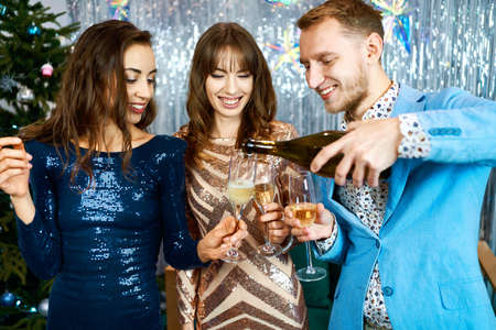happy festive friends celebrating christmas or new year together and looking happy, pouring sparkling vine into glasses