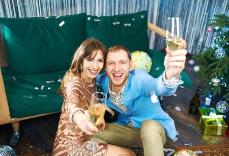 cheerful couple with glasses of champagne looking to camera, celebrating christmas or new year at home together Imagens