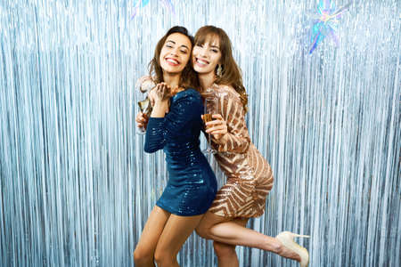 Portrait two joyful girls in shiny dresses on celebration party with silver shiny background, holds glasses of champagne