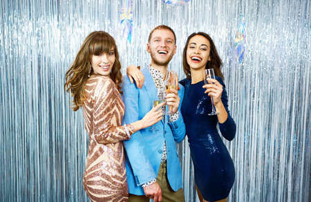 Portrait happy delited friends on celebration event on silver shiny background, holds glasses of champagne