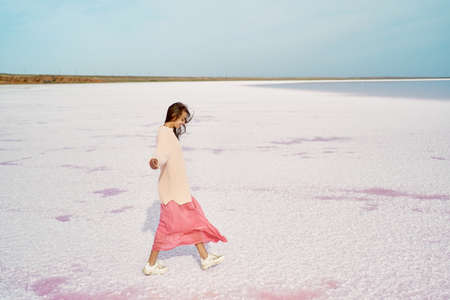 Side view walking girl in big sweater and blowing pink dress at beautiful landscape of salt flats at pink lake, feeling alive and happy