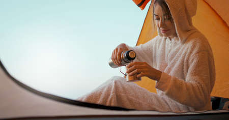 positive smiling woman in funny pajama like bunny in tent pouring warm coffee in mug. morning in camp during inner travel