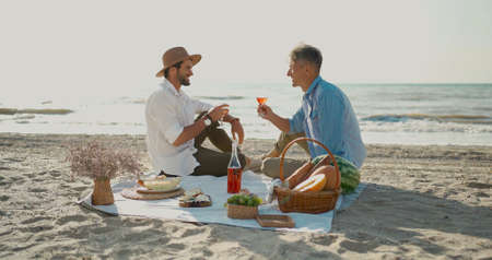 European happy gay couple drinking wine and enjoying romantic picnic at beach. Homosexual relationships and alternative love lifestyle concept Stock Photo