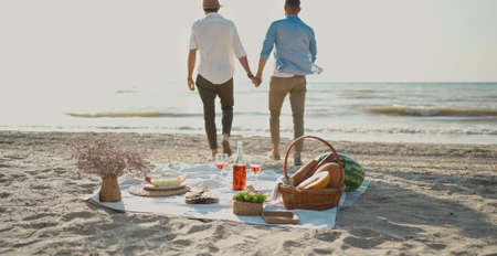 Silhouette gay couple walking by sea beach, focus on picnic blanket with wine, glasses and food. Romance, dating and lgbt love concept
