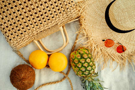 Beach summer female fashion outfit and tropical fruit flat lay. Close-up straw hat, straw bag, sunglasses, pineapple, coconut, grapefruit on blanket.