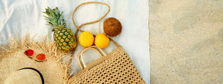 Panoramic banner image beach summer female accessories and tropical fruit flat lay. Top view straw hat, straw bag, sunglasses, pineapple, coconut, grapefruit on blanket at sandy beach.