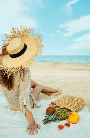 Rear view woman in big hat sitting on beach along the seashore. Stylish beach accessories and fresh fruit on blanket, summer vacation relaxing Stock Photo