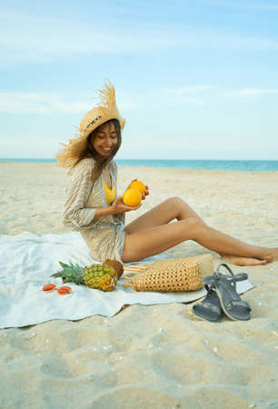 Stylish smiling woman in big hat sitting on sandy beach, holding grapefruits, having great time on summer vacation at seashore