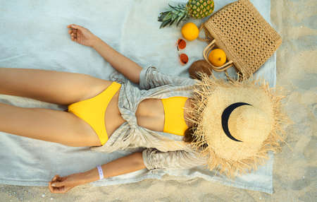 top view lying woman in yellow bikini covered head by straw hat, relaxing and sunbathing at beach during summer vacation