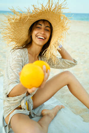 portrait summer woman in straw hat laughing and holding grapefruit on sandy beach by sea Stock Photo