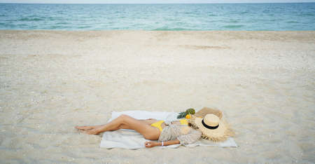 relaxing woman lying and sunbathing at beach, beach accessories and fresh fruit on blanket