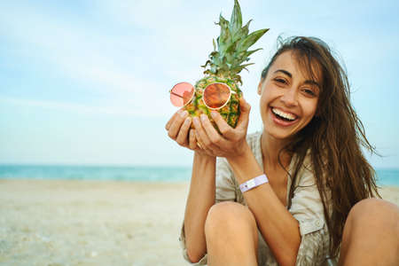 emotional portrait laughing woman on beach holding pineapple in red sunglasses