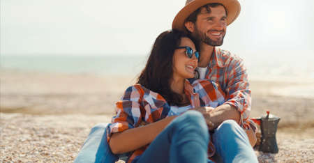 happy romantic couple sits on sea beach, talks, laughs and hugs. moments of love Stock Photo