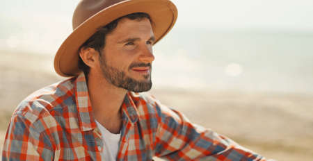 close up portrait of handsome stylish casual man traveler in hat sitting at sea coastline and enjoying peaceful nature
