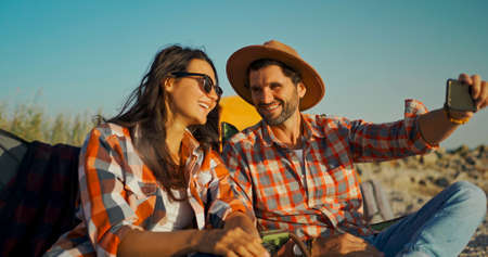 carefree couple happy travelers calling or making video call to, camping relax vacation