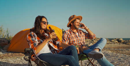 carefree couple freelancers relaxing with beer on seaside and Talking Smartphone Call To friends or family Stock Photo