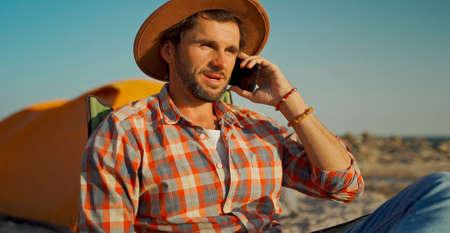 happy carefree Businessman in hat Talking Smartphone Call To Colleagues during camping rest.