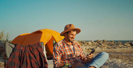 carefree freelancer man enjoying camping, using smartphone, networking, online surfing