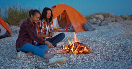 esbian couple roasting vegetables on fire, sitting on beach next to tent in camping.