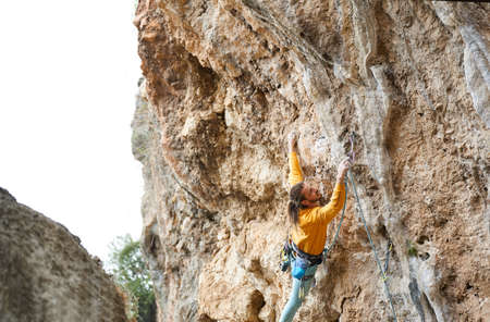 Strong man climber climbing on the rock route, making hard wide move and cliping rope Stock Photo