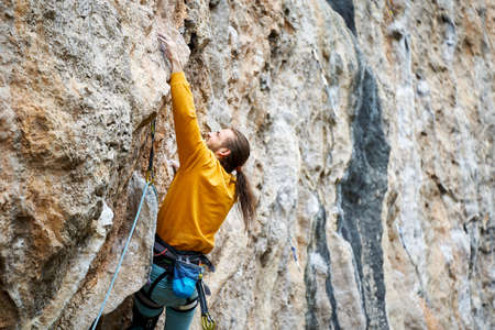 close up man climber climbing on high rock gliff, making hard move up, gripping hold Stock Photo