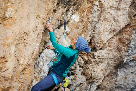 Woman climber exploring challenging route on cliff in cold weather Stock Photo