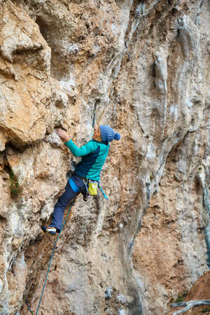 woman rock climber climbs on a rocky wall, reaching holds and gripping hold.