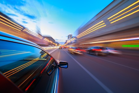 The car moves at fast speed at the night. Blured road with lights with car on high speed. Stock Photo