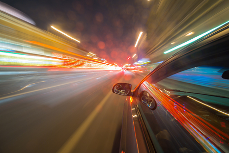accelerated: View from Side of Car moving in a night city, Blured road with lights with car on high speed. Concept rapid rhythm of a modern city.
