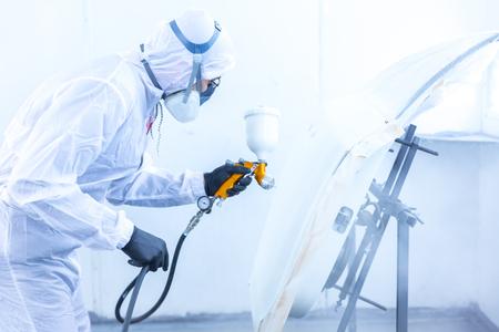 Automobil-Arbeiter Maler in Schutz-Arbeitskleidung und Atemschutzmaske Karosserie Elemente in Lackkammer Standard-Bild - 71246580