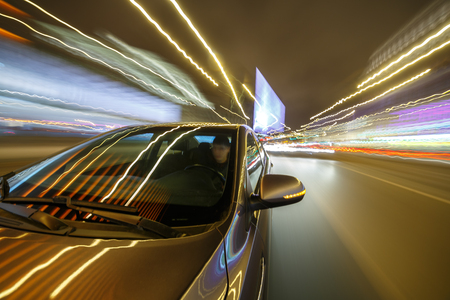 Blurred urban look from fast driving car to back side and driver at winter night. Longexposure shot.