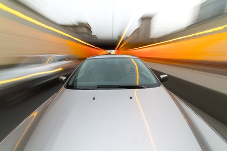 accelerated: Front view of black car driving on high speed on a city at day time.