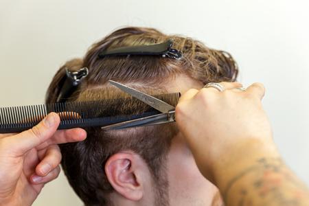 Skillful professional hairdresser cutting male hair. Closeup shot.