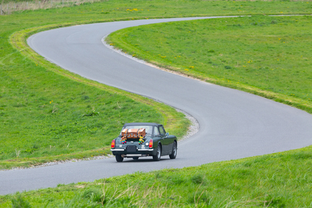 Old british car with trunk and toys on back side driving on S-curved road near Stonehenge, England.